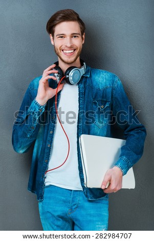 Everything I need is always in hand. Happy young man holding laptop and smiling at camera while standing against grey background - stock photo