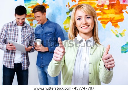 Everything is great. Confident young woman show you thumbs up and looking at camera with smile while his colleagues talking in the background. - stock photo