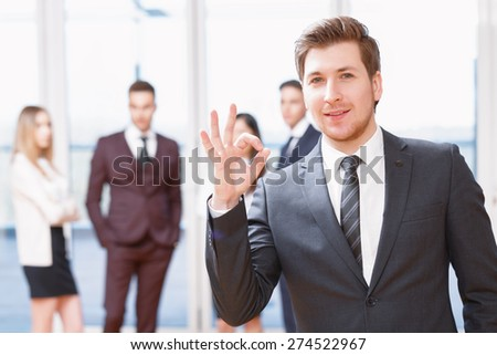 Everything is ok.  Young business man standing in foreground smiling and showing OK, his co-workers discussing business matters in the background - stock photo