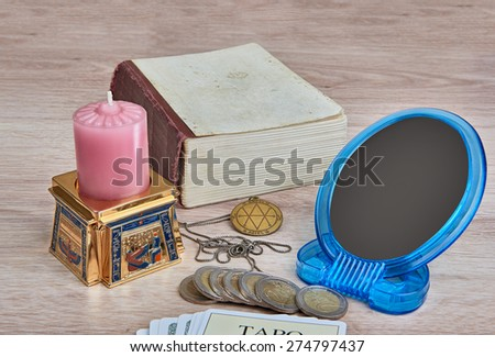 Everything is ready for divination - pack of Tarot cards, pentacle medallion, candle in  Egyptian candlestick, mirror, book and coins are on the table - stock photo