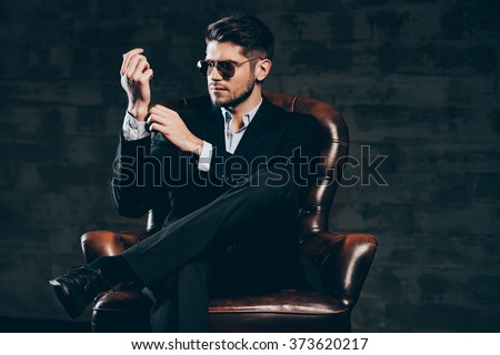 Everything must be perfect.Young handsome man in suit and sunglasses adjusting sleeve on his shirt while sitting in leather chair against dark grey background - stock photo