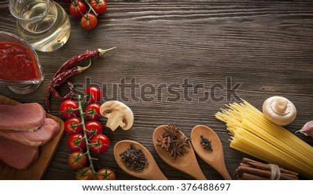 everything on wood table for the cooking of acute Italian sauce (tomato garlic spices olive oil) flat lay - stock photo
