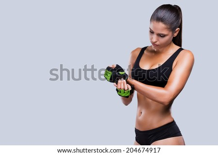 Everything should be perfect. Beautiful young sporty woman with perfect body adjusting her sports gloves while standing against grey background - stock photo