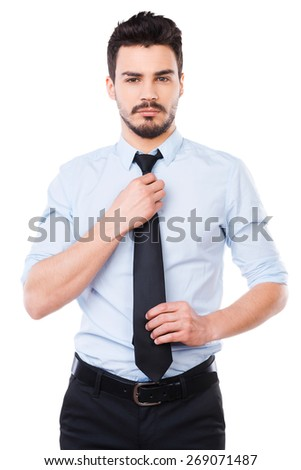 Everything should be perfect. Confident young man in shirt and tie looking at camera and adjusting his necktie while standing against white background - stock photo