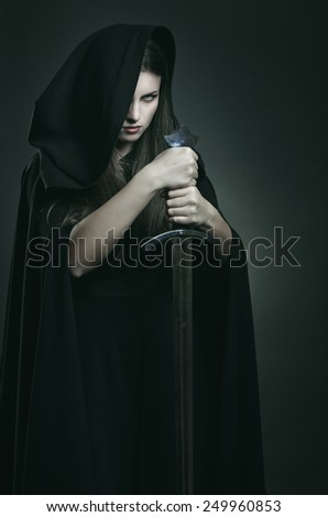 Evil expression of beautiful dark woman with  sword . Fantasy and legend  - stock photo