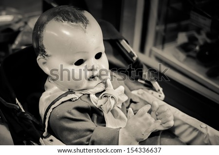 Evil Eyeless Baby Doll in an Antique Cot - stock photo