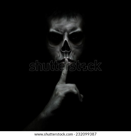 Evil man gesturing silence, quiet isolated on black background - stock photo