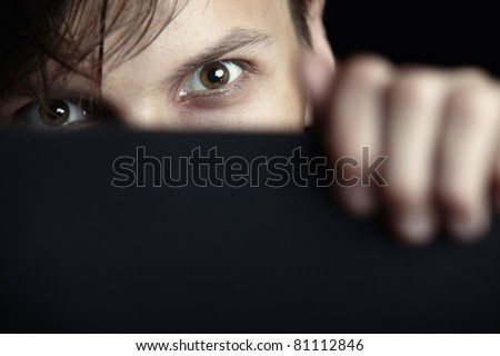 Evil man hides behind the black board and observes - stock photo