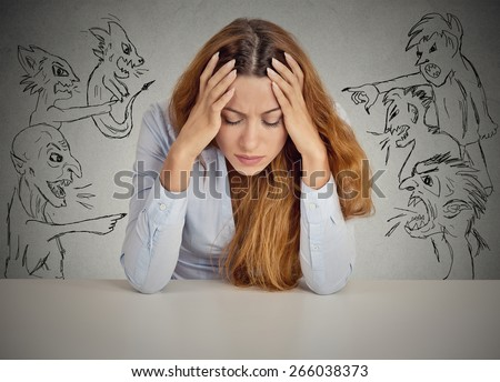 Evil Men pointing at stressed woman. Desperate young businesswoman sitting at desk in her office isolated on grey wall background. Negative human emotions face expression feelings life perception - stock photo