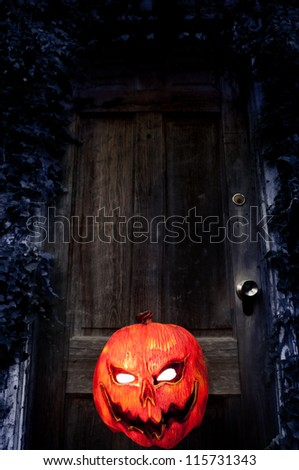 Evil Pumpkin - Jack O Lantern in front of Old Door - stock photo