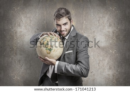 evil young business man holding a world globe against a grunge wall - stock photo