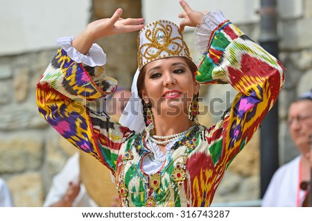 EVOLENE, SWITZERLAND - AUGUST 13: Beautiful Uzbekistani dancing girl from Issar in the CIME mountain culture Festival: August 13, 2015 in Evolene, Switzerland - stock photo