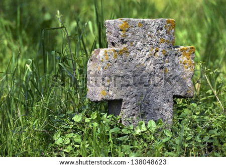 Exalted old stone cross in Macedonia cemetery - stock photo