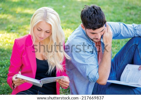 Exam preparation. Couple of students sitting on the grass and reading a book while teaching lessons on a break near the university building - stock photo