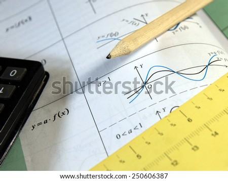 Exam, test study of mathematics (book, pencil, measure, calculator) - Background shows trigonometry formulas ans sinus graph - stock photo