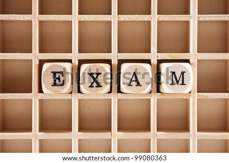 Exam word construction with letter blocks / cubes and a shallow depth of field - stock photo