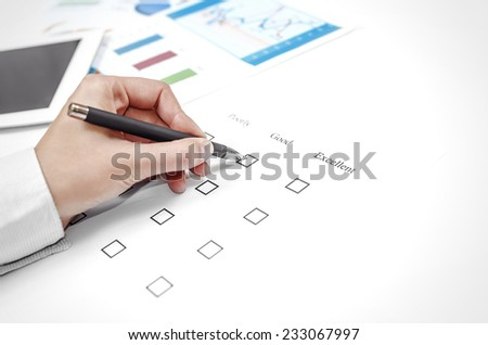 Examination paper on the office desk. Hand marks the estimate. - stock photo