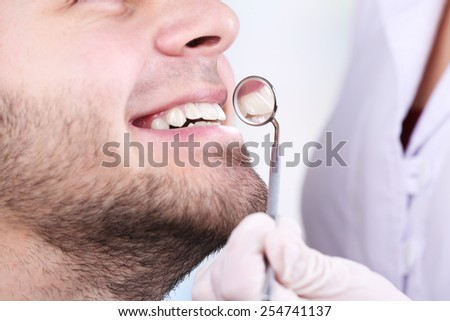 Examine of young man by dentist on white blurred background - stock photo