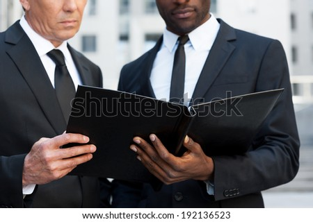 Examining documents. Cropped image of two confident business men looking at the note pad while standing outdoors - stock photo
