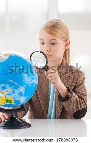 Examining globe. Concentrated little girl in formalwear examining globe with a loupe while sitting at the table - stock photo