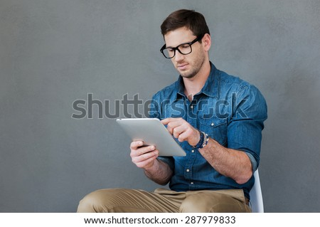 Examining his new gadget. Confident young man holding digital tablet while sitting against grey background - stock photo
