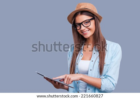 Examining new tablet. Beautiful young girl working on digital tablet and looking at camera while standing against grey background - stock photo