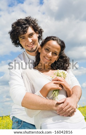 Example of harmony in love: young man hugging charming lady in white clothing while both looking at camera with happy smiles - stock photo
