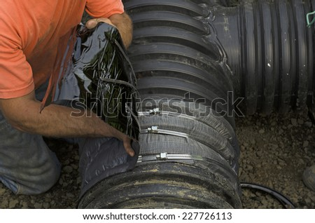 Excavation contractor uses a field repair coupler tape gasket to install a tee in plastic drain pipe for a new commercial street storm drain sewer - stock photo