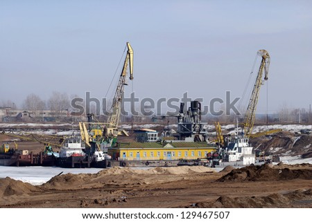 Excavation tractors on the river in the spring - stock photo