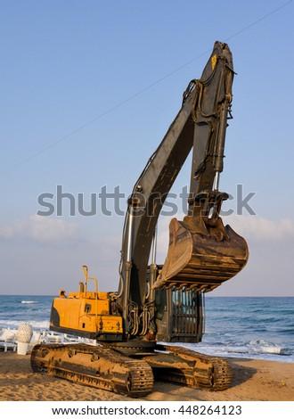 Excavator along the beach - stock photo