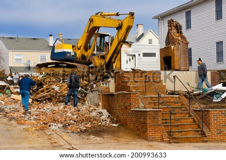 excavator and a ruined building on the construction site - stock photo