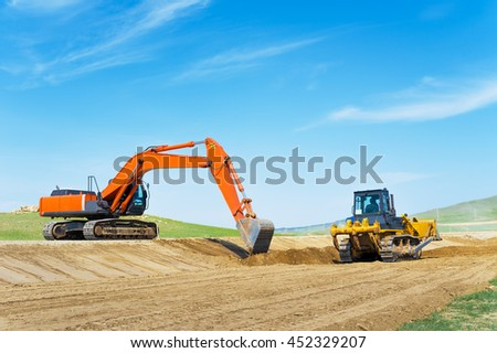 Excavator and bulldozer on road construction  - stock photo