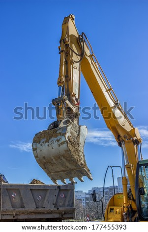excavator arm and dumper truck, digging trench for sewer line - stock photo