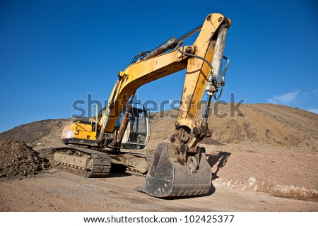 Excavator at a construction site with blue sky - stock photo