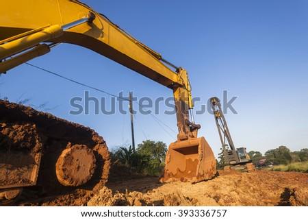 Excavator Bin Crane Earthworks Industrial machines Excavator bin and mobile crane construction on site earthworks. - stock photo