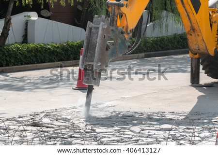 Excavator breaking and drilling the concrete road for repairing - stock photo