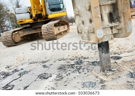 Excavator breaking street asphalt with hydrohammer drill at repairing roadwork - stock photo