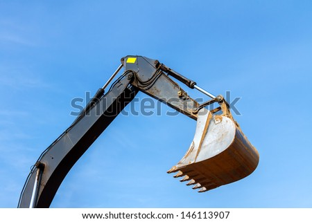 Excavator Bucket across the Blue Sky - stock photo