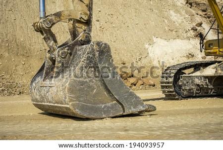 Excavator bucket and tracks - stock photo