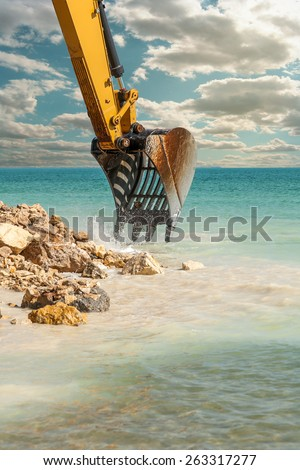 Excavator bucket dredging sand and gravel from the seafront - stock photo