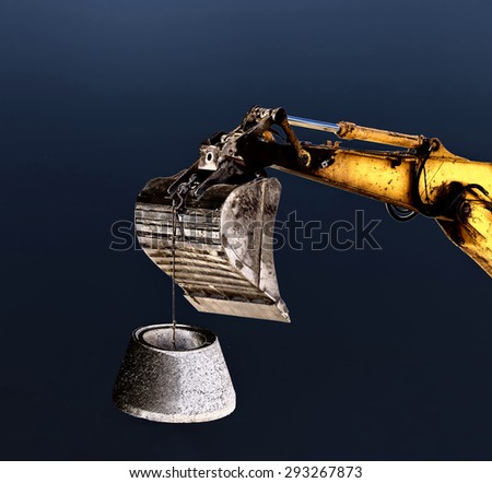 Excavator bucket lifting concrete element for manhole on dark background - stock photo