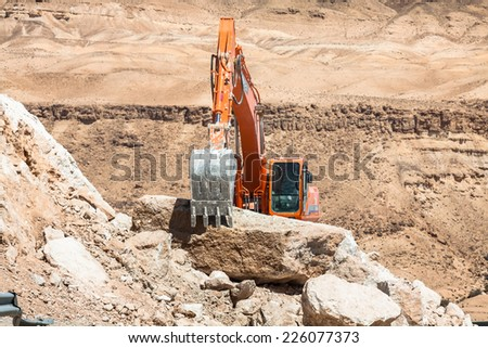 Excavator building a mountain road in the atlas mountain - stock photo