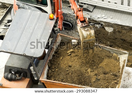 excavator  carrying debris into a construction  dumper  truck , chimpin, in city street  - stock photo