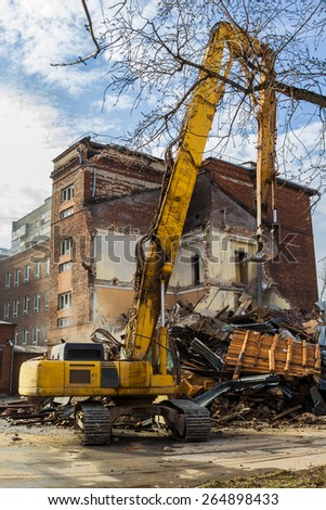 excavator demolishes old soviet school building in moscow - stock photo