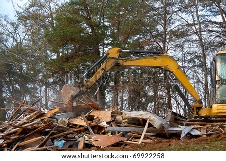 Excavator demolition on old building - stock photo
