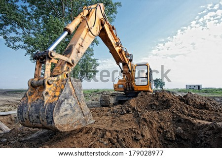 excavator digging a trench on the site, focus on the excavator back - stock photo