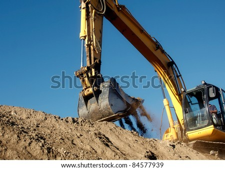 Excavator digging the earth with the sky in the background - stock photo