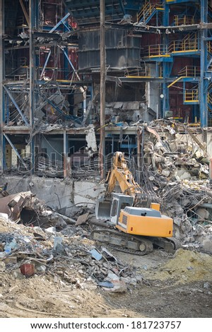 Excavator in front of a big metal construction destroyed - stock photo