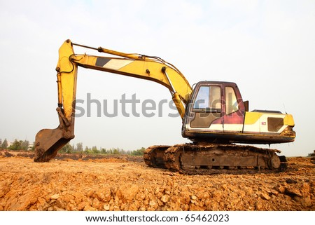 excavator loader machine during earthmoving works outdoors at construction site - stock photo