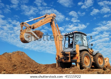Excavator Loader with rised backhoe standing in sandpit with over cloudscape sky - stock photo